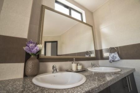 Baños con cerámicas de piso a techo lo convierten en un cuarto de baño bastante iluminado. Casa Modelo Capella
